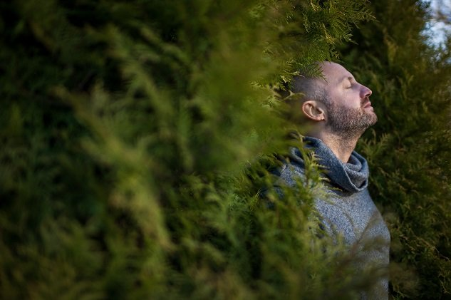 A bald man in a warm sweater is resting, leaning against the trees breathing fresh air in nature.